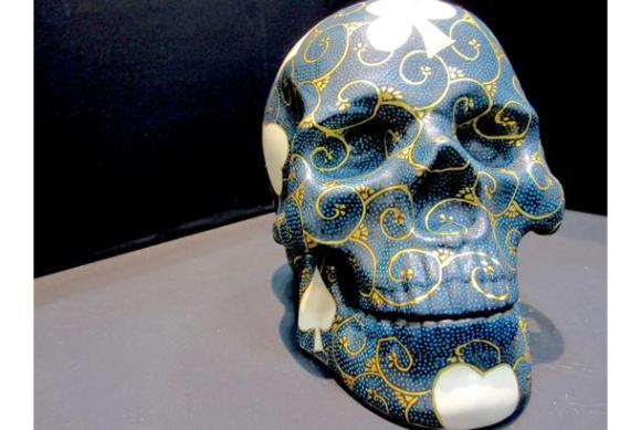 """This skull features playing card suits and a style of blue dots particular to Kutani ware called """"ao tsubu"""". The piece is said to drive away bad luck."""