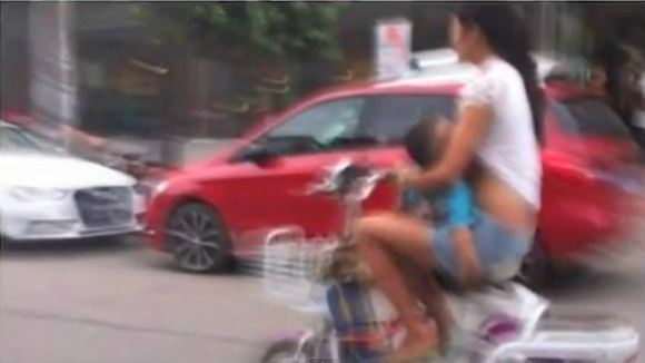 Chinese woman pulled over for breastfeeding her child while riding a moped