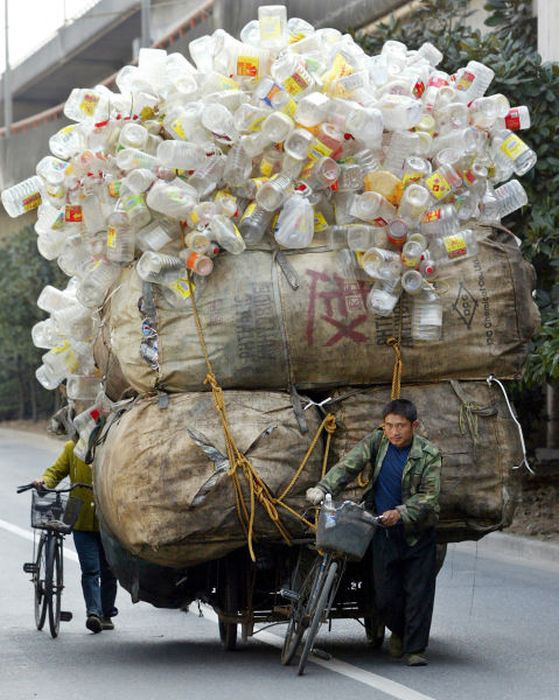 A CHINESE MAN PUSHES HIS BICYCLE TRANSPORTING RECYCLABLE PLASTIC IN SHANGHAI.