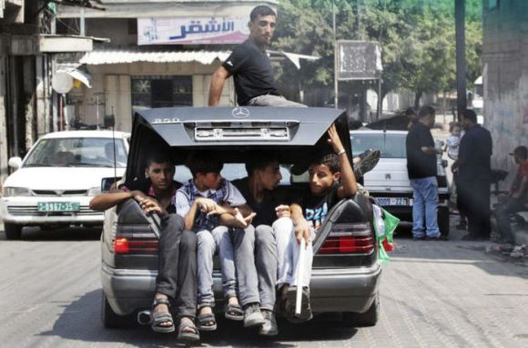 Palestinians sit in the boot of a car as they follow the convoy of released Palestinian soccer player Al-Sarsak upon his arrival in Gaza