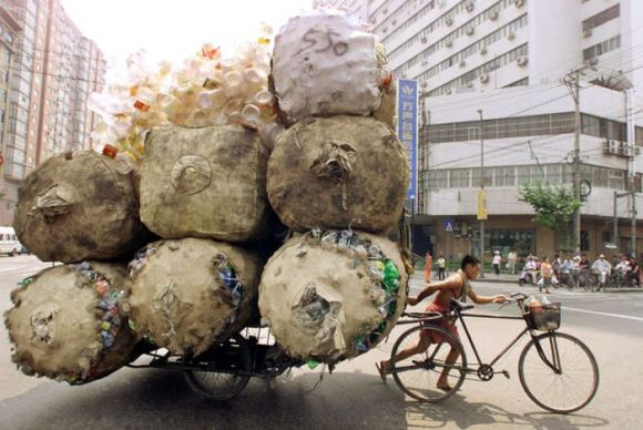 A CHINESE MAN PULLS A CART PACKED HIGH WITH BAGS OF PLASTIC CONTAINERSIN SHANGHAI.