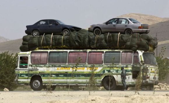 A bus is driven past a market in Maidan Shahr, capital of Wardak Province