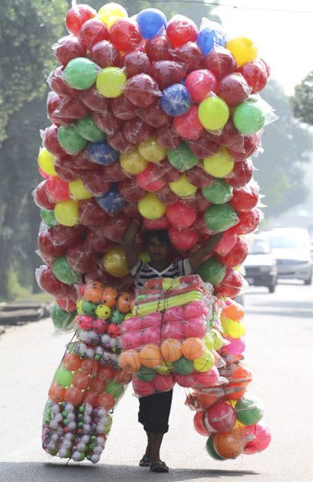 A vendor carries plastic balls for sale as he walks down the streets of Noida