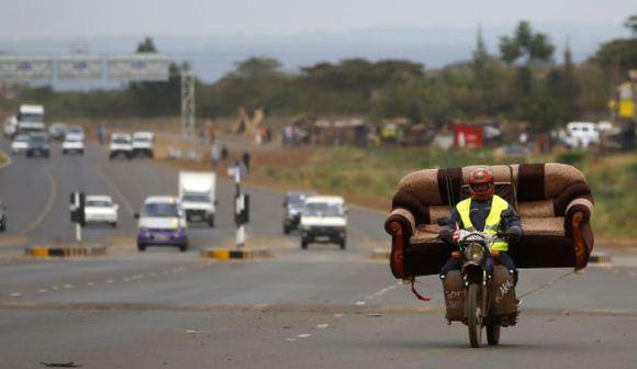 A man carries a sofa on his motorcycle on a highway near Kenya's capital Nairobi