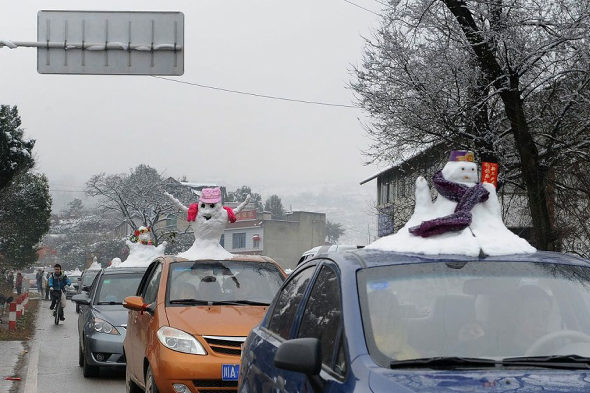 Local residents in China sell cartop snowmen to tourists