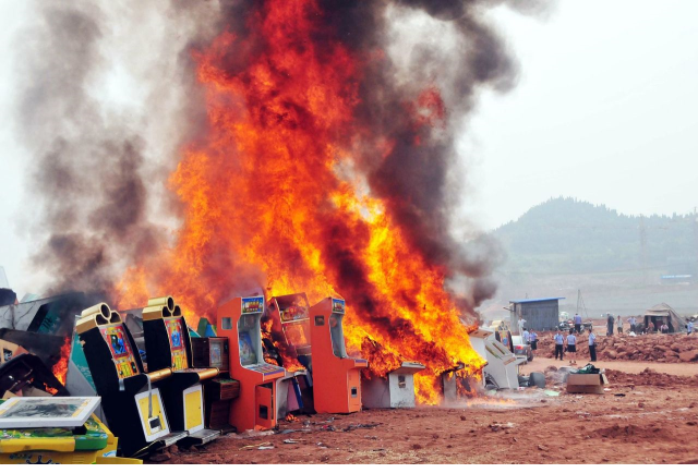 Why are these Chinese police officers torching dozens of arcade cabinets?