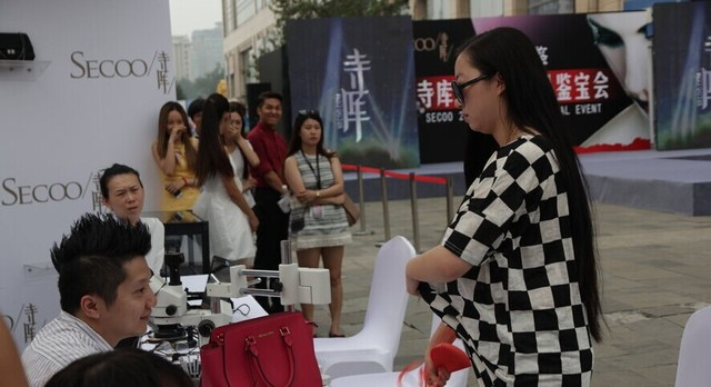 Chinese woman removes her bra in public at a luxury appraisal event in Beijing