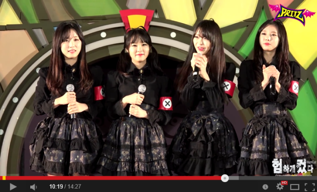 Korean idol unit trots on stage in matching skirts and what look like pseudo-Nazi armbands