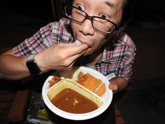 Mr. Sato eats curry with his hands on a park bench because spoons are for losers