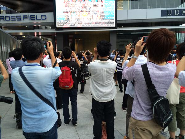Just a photo of otaku taking video of video of people dressed like anime idols to promote movie