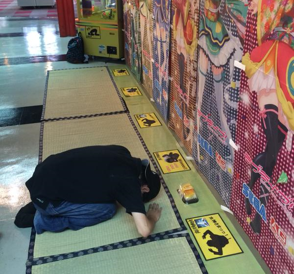 Japanese arcade has floor pads so fans can kneel before, leave offerings to their anime crushes