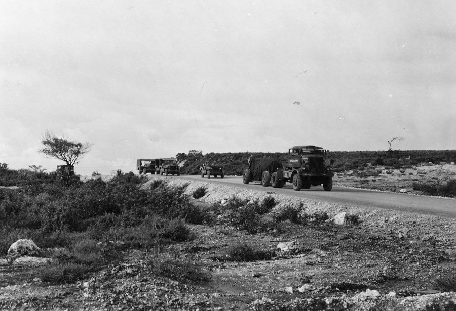 the-bomb-is-then-escorted-to-the-nearby-north-field-airbase-on-tinian-shrouded-in-tarp