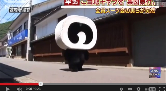 Roll cake-headed town mascot character attacked by group of men, woman inside injured