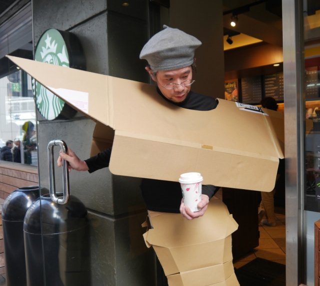 Mr. Sato hits the streets to show off his new cardboard fashion!