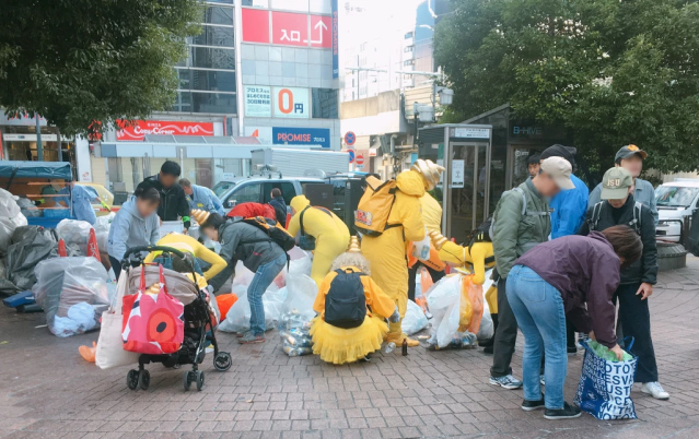 The morning after: Volunteers clean up the litter from Tokyo's Halloween street party
