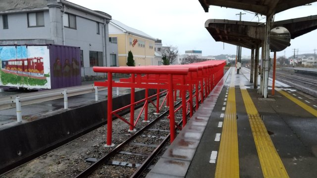 The Japanese train station with torii gates on its tracks